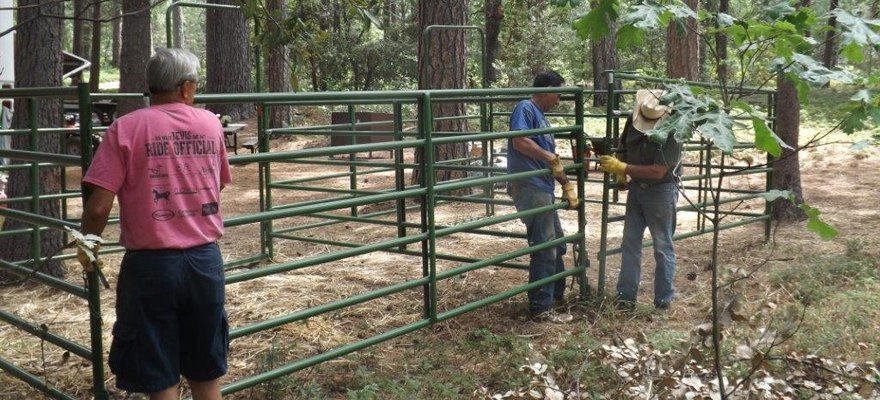 Two guys installing a corral